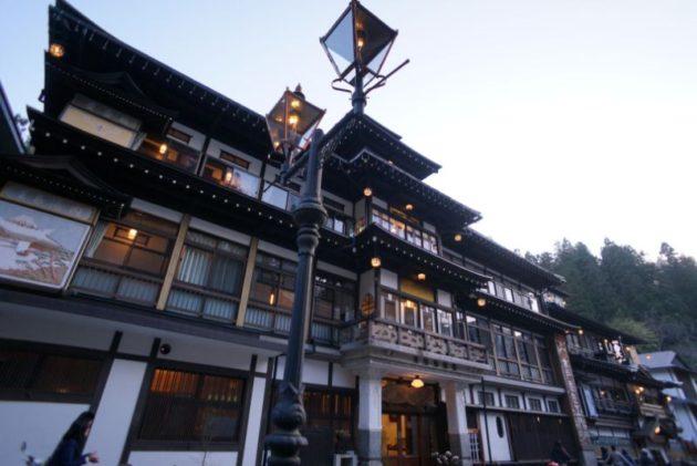 陽が傾き始めて銀山温泉のライトが灯る3